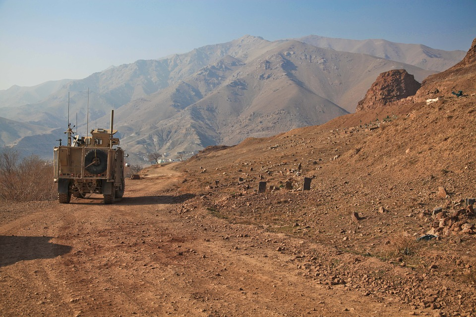 Armored vehicle driving on dirt track with mountains in the distance