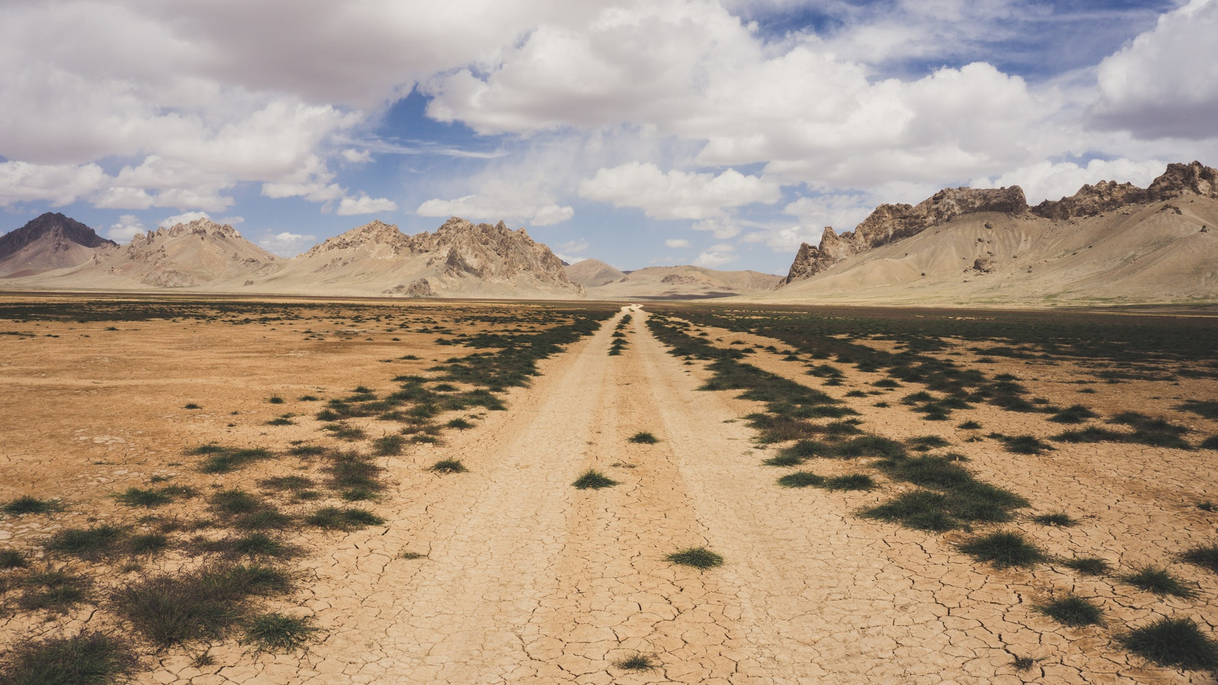 Dirt road in the desert with mountains in the distance
