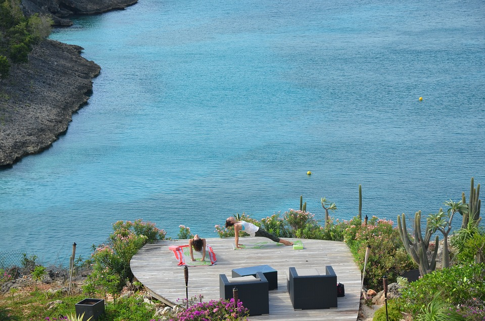 People practicing yoga on a patio overlooking cliffs and Caribbean waters