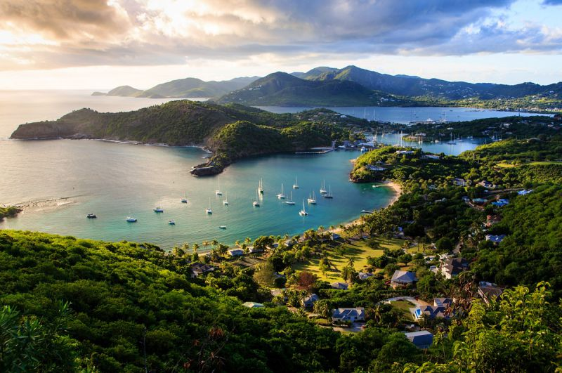 Bird eye view of a harbor in Antigua and Barbuda with docked yachts and a village on the coast