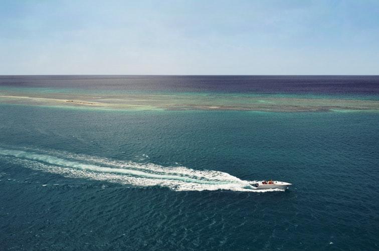 Motor boat passing coral reef