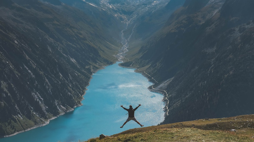 Man jumping up on the edge of a mountain with a lake in the valley in the distance