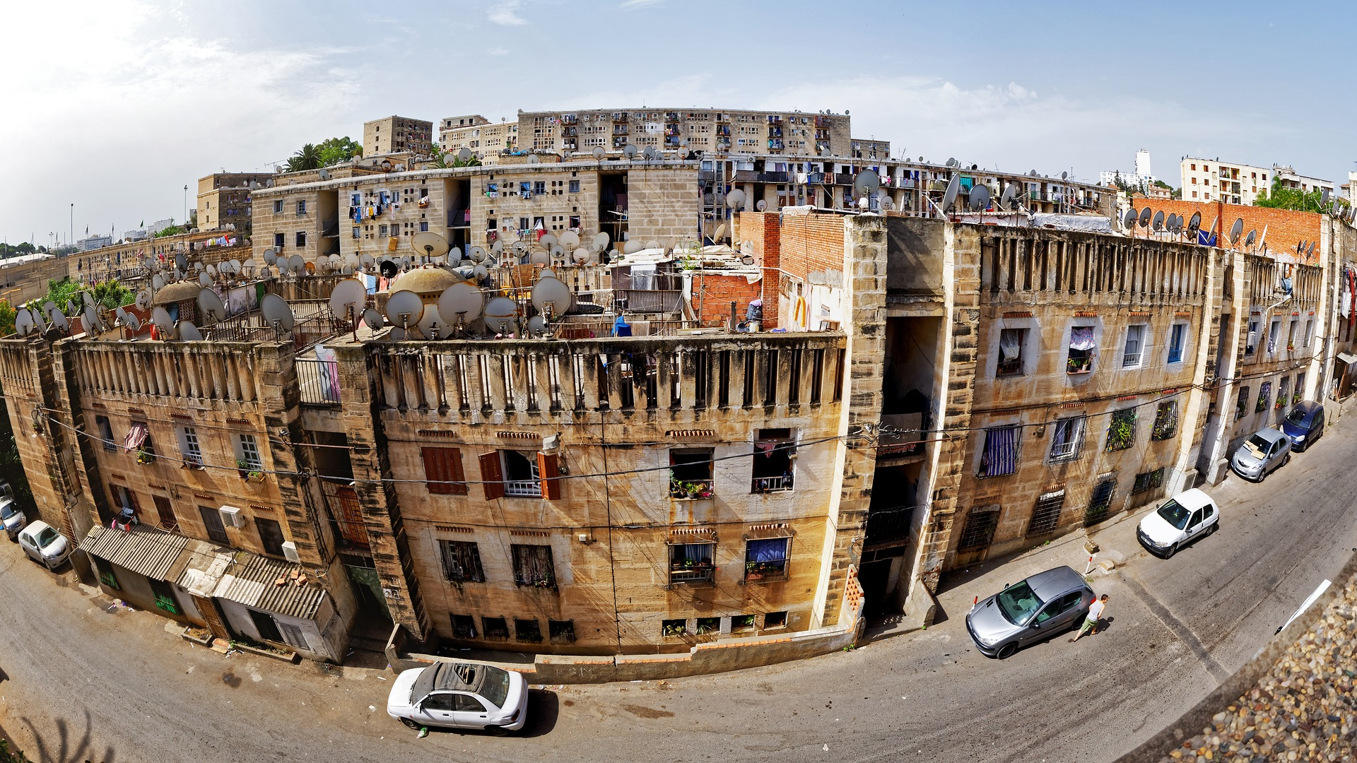 Panoramic image of old Algerian housing blocks with cars parked on the street