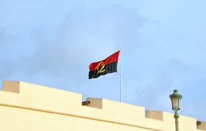 Angolan Flag mounted on top a city wall with blue sky in the background