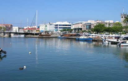 A harbor in barbados with boats and buildings in the background