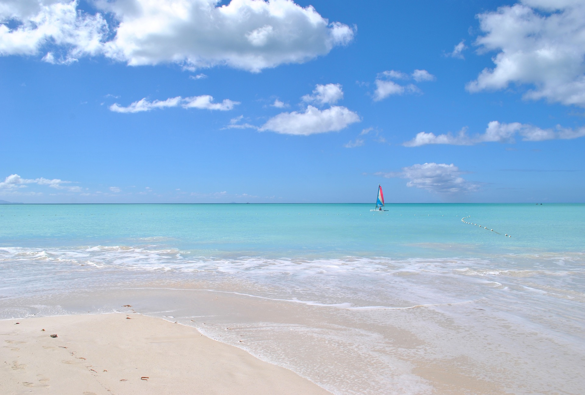 Person windsurfing in the distance in the turquoise waters of the Caribbean