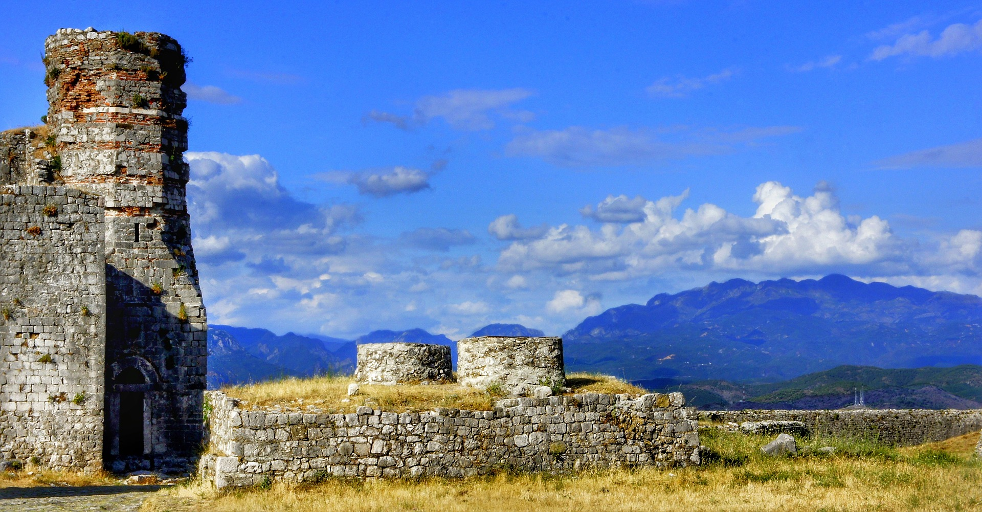 Ruins of a castle with mountains in the distance