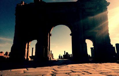 Sunset setting on Ruins of Roman arch in Algerian desert