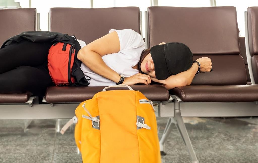 The woman is sleeping in airport terminal and waiting for airplane arrival; delayed aeroplane concept.