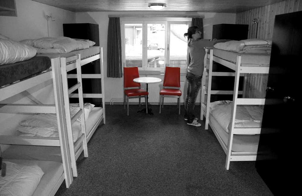 Gray picutre of bunk beds in a hostel room with contrasting red chairs