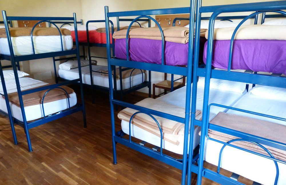 Several bunk beds with blue frames inside a hostel room