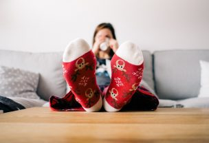 Woman sitting on a couch drinking from a mug and holding her feet in red socks up on the table