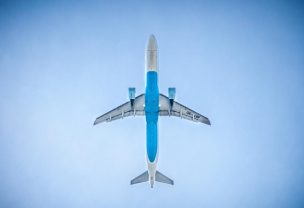Image of passenger airplane taken from the ground looking at the bottom of it