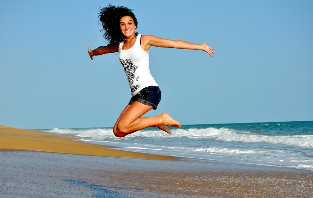 Woman jumping up into the air on a beach