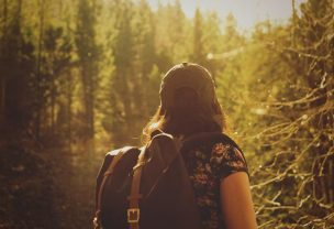 Image of a solo female hiker looking at forest in the distance