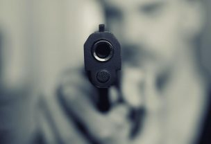Image of a man pointing a gun directly at the viewer
