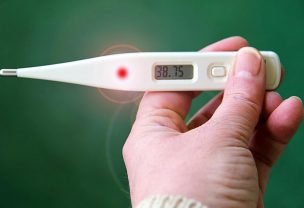 Person holding a thermometer with 38.7 degrees Celsius on it