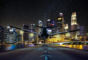 Image of a passenger plane landing on an airport with skyscrapers in the distance