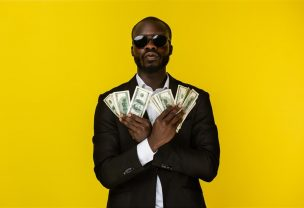 bearded luxury young afroamerican guy is holding lots of money in both hands in sunglasses and black suit on the yellow background