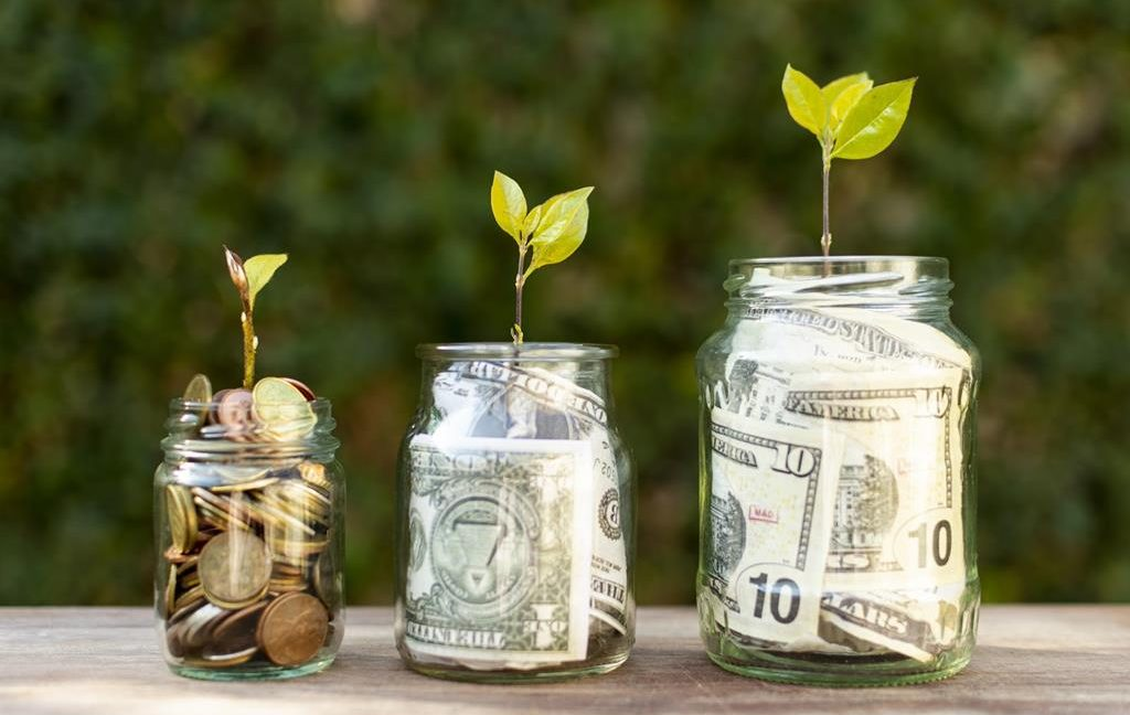 Small plants sprouting out of glass jars filled with paper money and coins