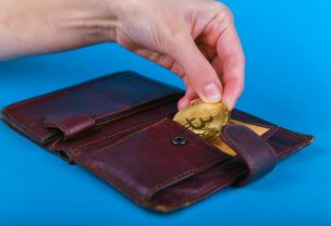 Inserting the coin into the leather wallet