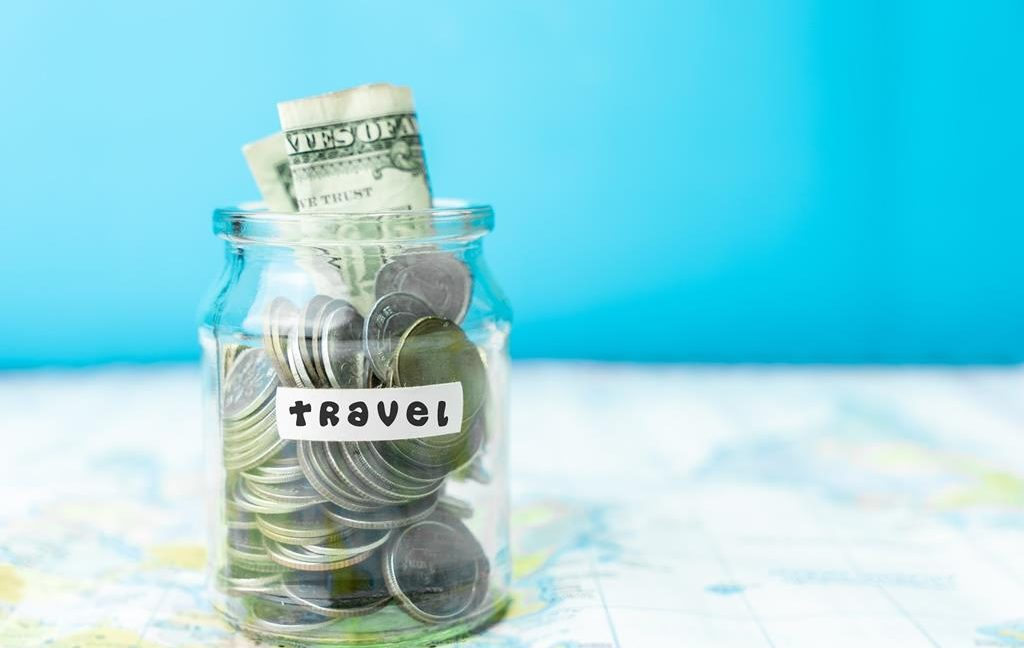 Saving money in a glass jar for travel on map