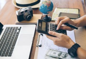 Close up the hands of travelers using a calculator to calculate travel expenses. Planning a trip,copy space. Travel background