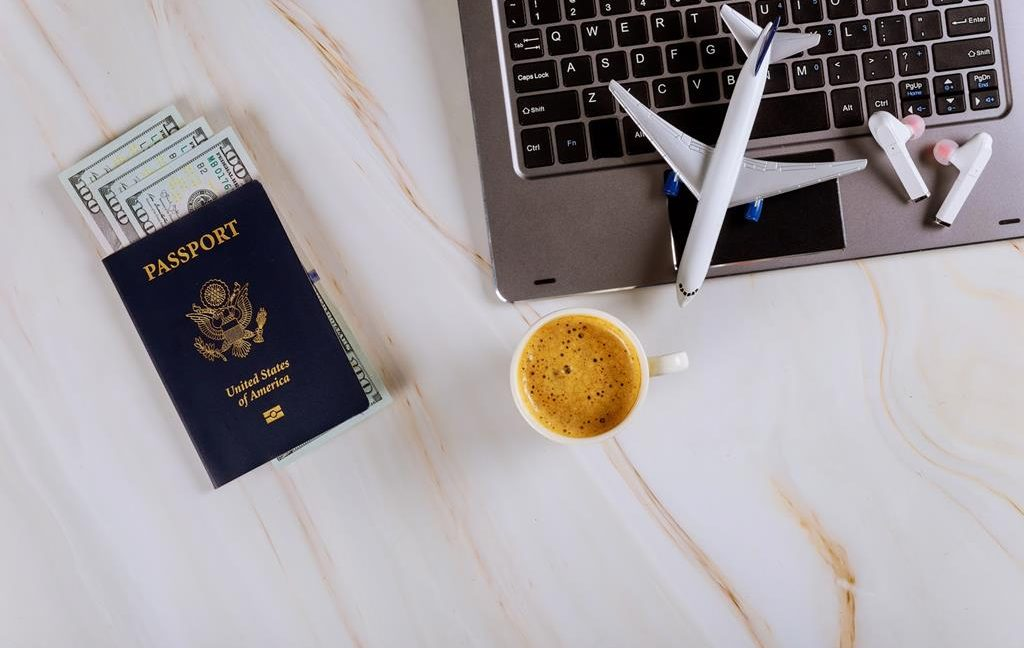 Passport with money inside sitting beside a laptop with a passenger plane sitting on top of a laptop and a coffee mug beside