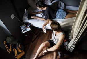 Caucasian backpackers in a shared bedroom hostel