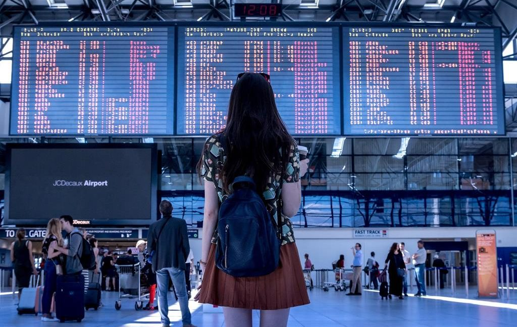 Image of a woman looking at departure board in an airport
