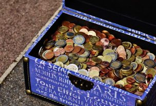 A blue opened box with white writing on it filled up with coins