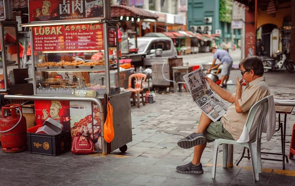 A local man reading a newspaper in the street sitting on a plastic chair with a busy street in the background