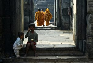 Kids sitting on the entrance stairs of the temple and monks in background