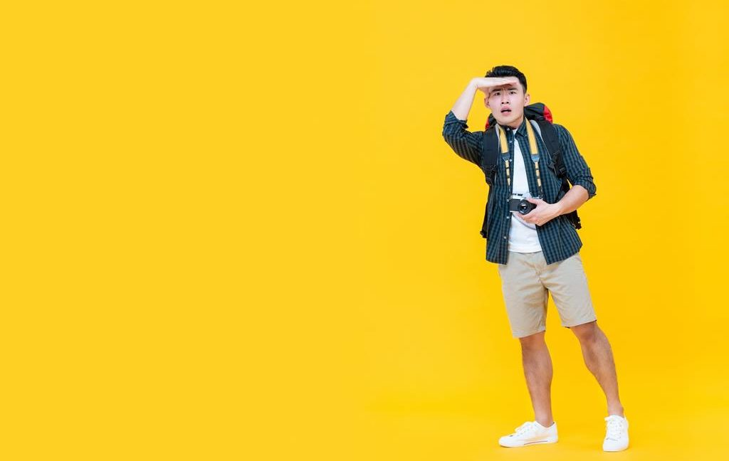 Asian tourist man looking away with hand on forehead isolated on yellow background with copy space