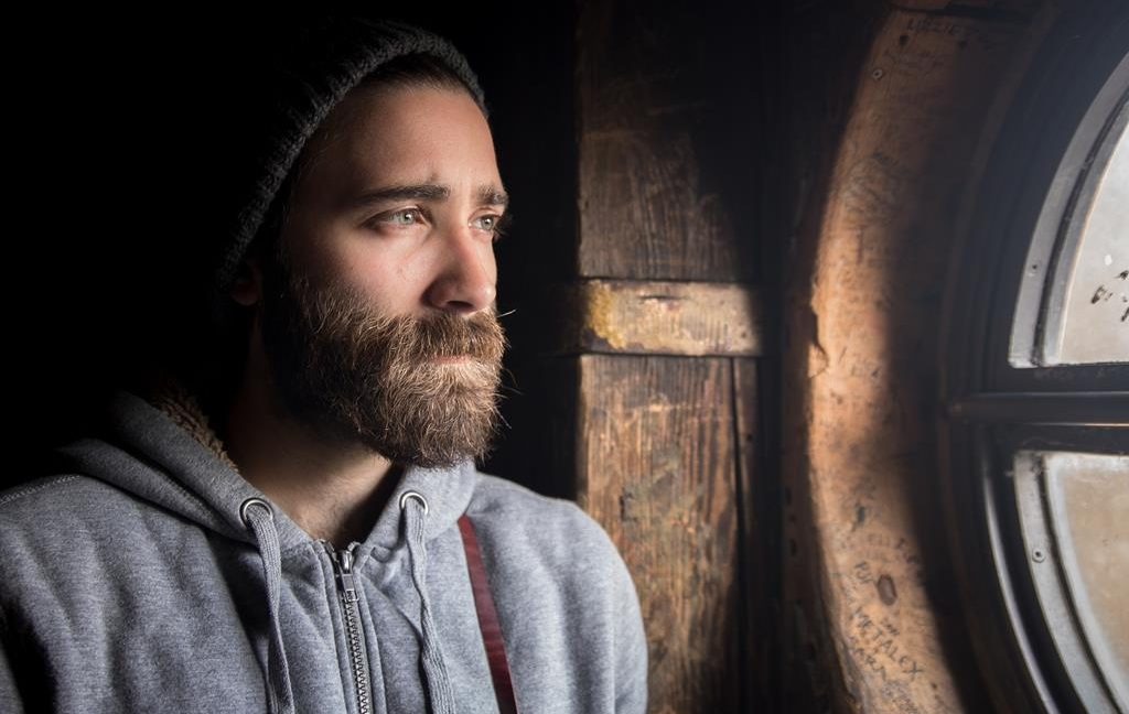 Image of a bearded man in a beanie looking through the window with a longing expression