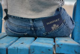 Image of a person sitting down on a bench with their passport in back pocket